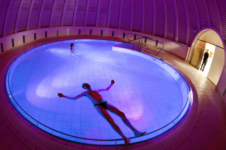 Ein Gast des Thermalbades Toskana Therme liegt im salzhaltigen Wasser eines runden Schwimmbeckens unter farbiger Beleuchtung und lauscht den Unterwasser-Klängen der Musik.