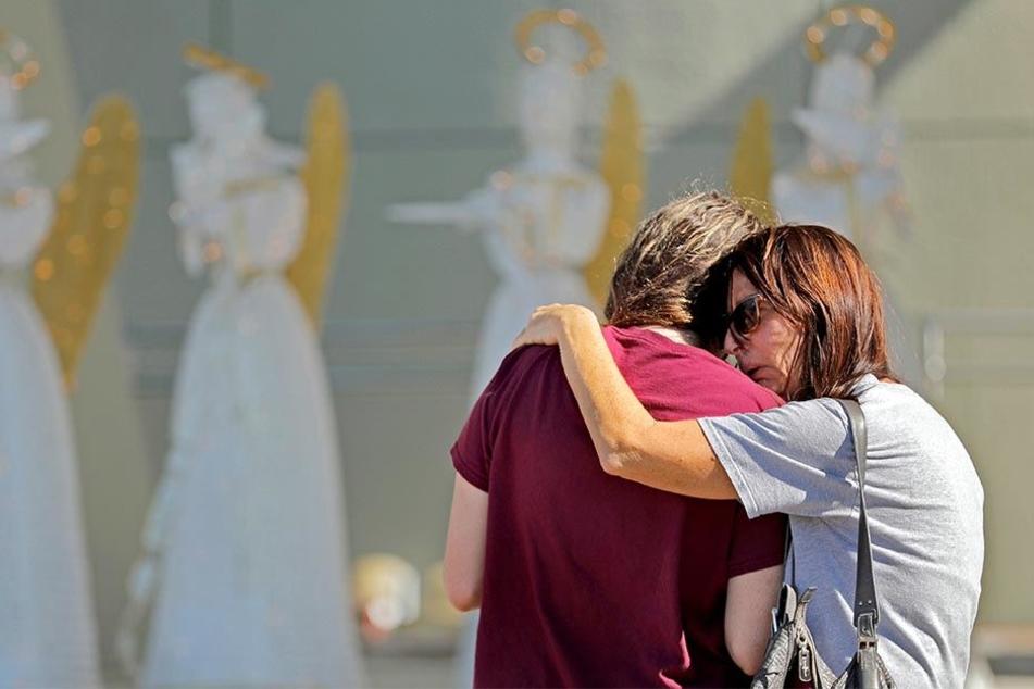 Von Trauer überwältigt, gedenken zahlreiche Menschen den Opfern des Amoklaufs.