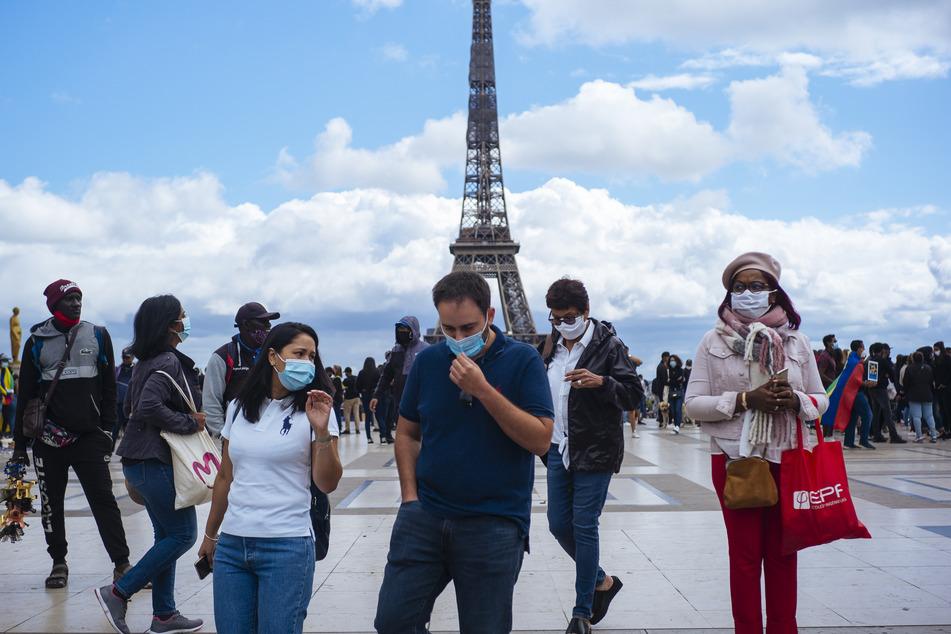 Passanten tragen am Platz Trocadero in der Nähe des Eiffelturms Mundschutze und Gesichtsmasken. In Paris gilt wegen steigender Fallzahlen eine Maskenpflicht im öffentlichen Raum.