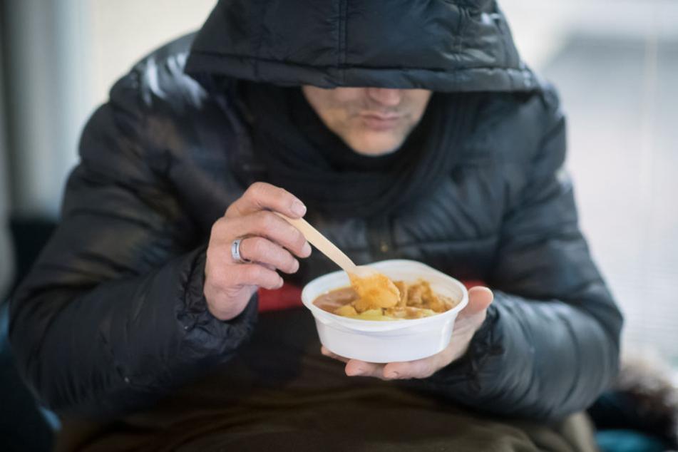 Ein Obdachloser ist in einer Wärmestube eine Mahlzeit.