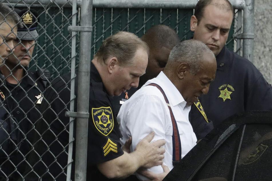 US-Entertainer Bill Cosby (Mitte) wird von Sicherheitskräften aus dem Gericht zu einem Auto geführt.