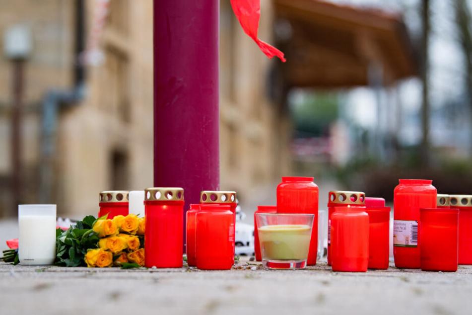 Kerzen und Blumen liegen vor dem Tatort.