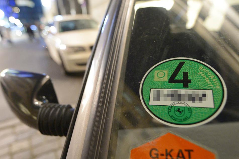 Eine grüne Umweltplakete ist an einem parkenden Fahrzeug in der Innenstadt angebracht. (Symbolbild)