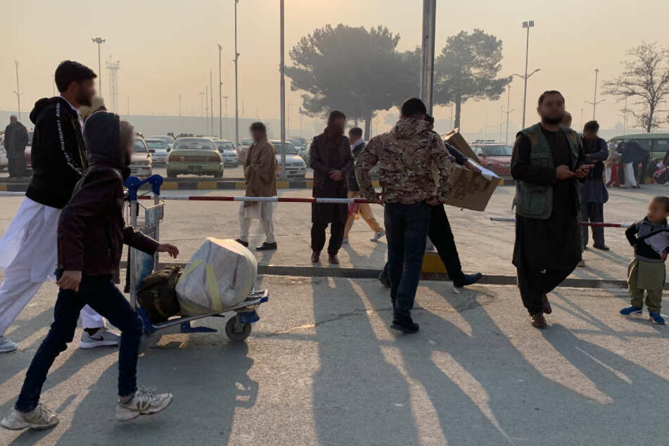 Die aus Deutschland abgeschobenen Afghanen verlassen nach ihrer Ankunft den Flughafen.