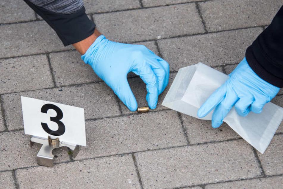 Einsatzbeamte heben die Patronenhülse auf und packen sie als Beweismittel in ein Päckchen.