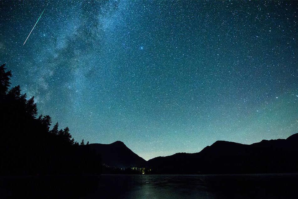 Eine Sternschnuppe leuchtet neben der Milchstraße am Himmel über dem Walchensee.