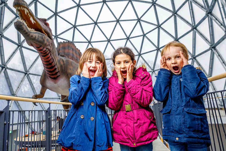 """""""Ahhhhhhh"""": Cally (8, v.l.), Julia (7) und Florian (8) haben gerade mit dem  Spinosaurus im Inneren des Eingangsportals Bekanntschaft gemacht."""
