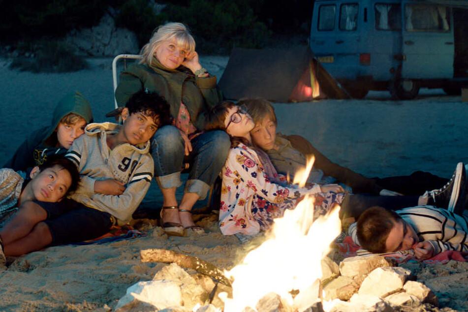 Fahim (Dritter von rechts, Assad Ahmed) und die anderen Kinder des Schachklubs am Abend beim Lagerfeuer am Strand mit Mathilde (M., Isabelle Nanty)