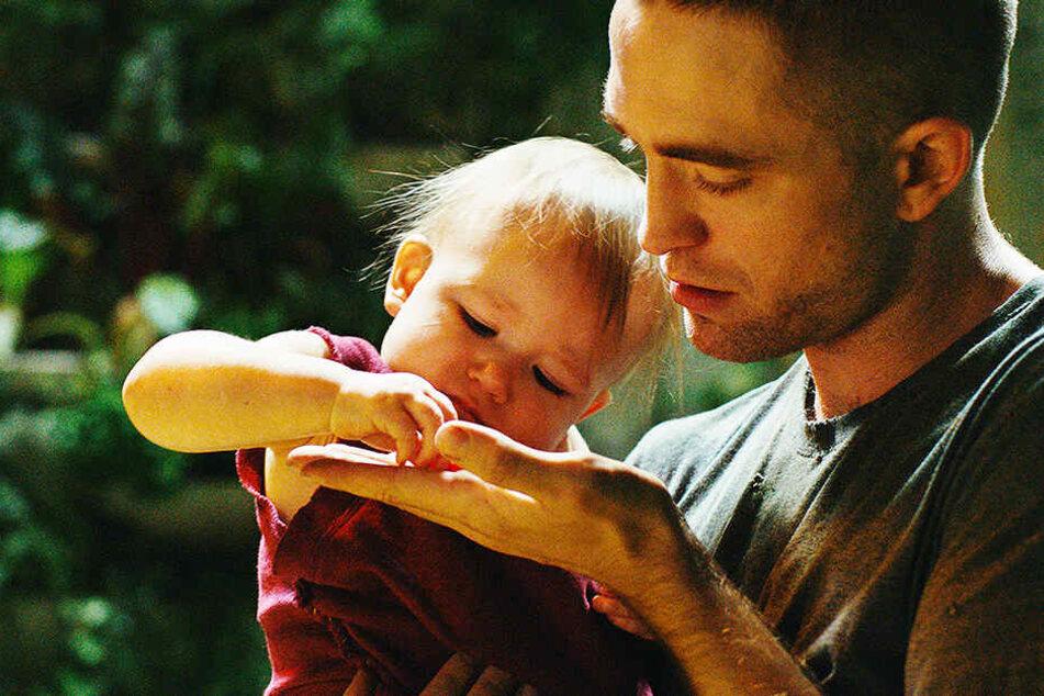 Monte (r., Robert Pattinson) kümmert sich liebevoll um seine Tochter Willow (Scarlett Lindsey).