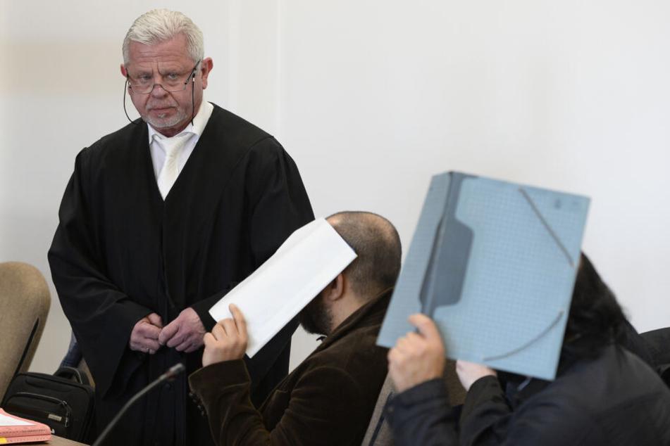 Die Angeklagten warten im Sitzungssaal des Kölner Landgerichts neben Anwalt Dieter Tomczyk auf den Beginn ihres Prozesses.