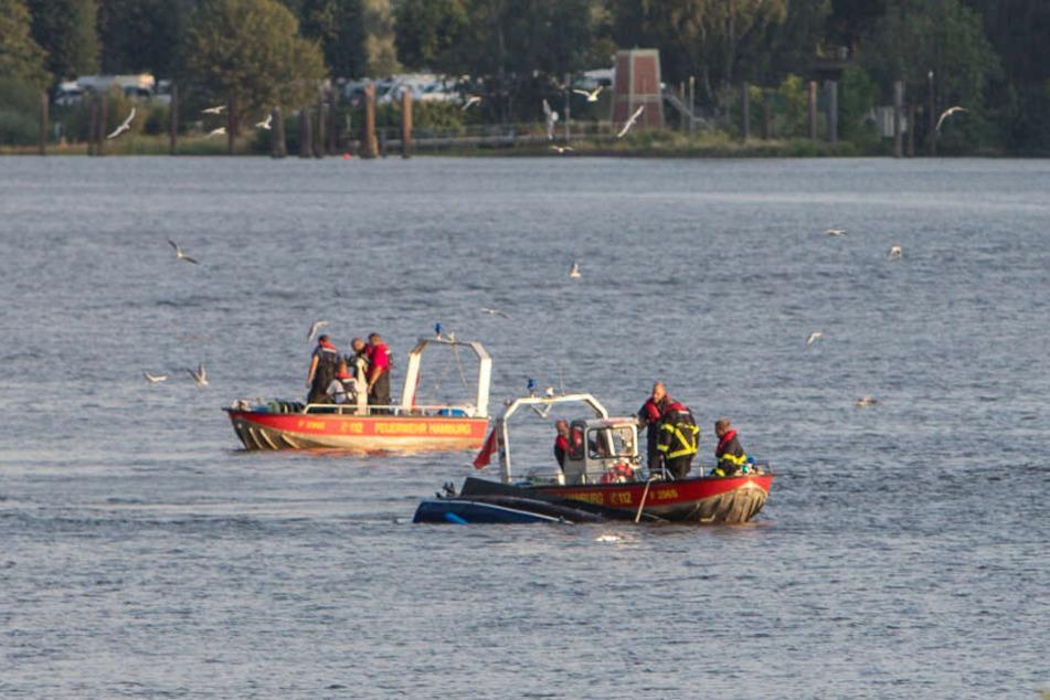 Feuerwehrboote sichern das kieloben treibende Boot.