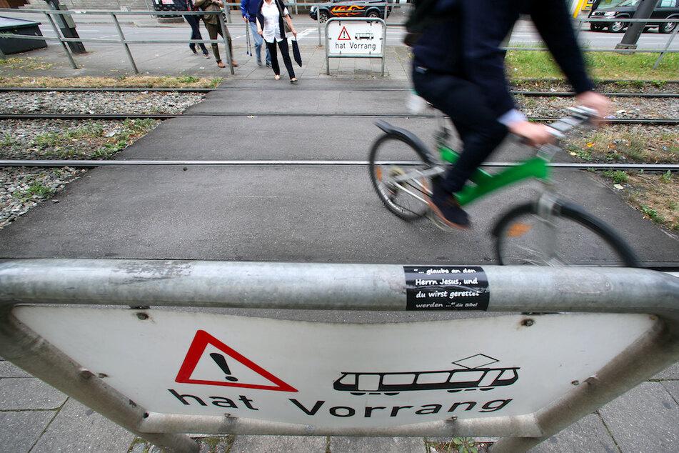 Radfahrer und Fußgänger queren Straßenbahnschienen in München.