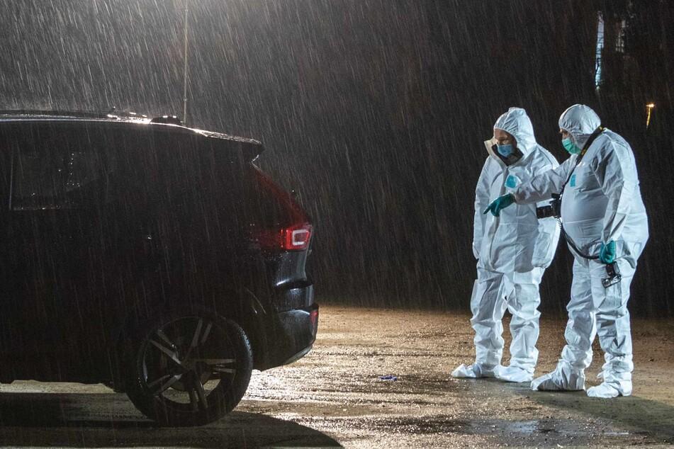 Mitarbeiter der Spurensicherung untersuchen auf einem Parkplatz den Fundort einer Frauenleiche.