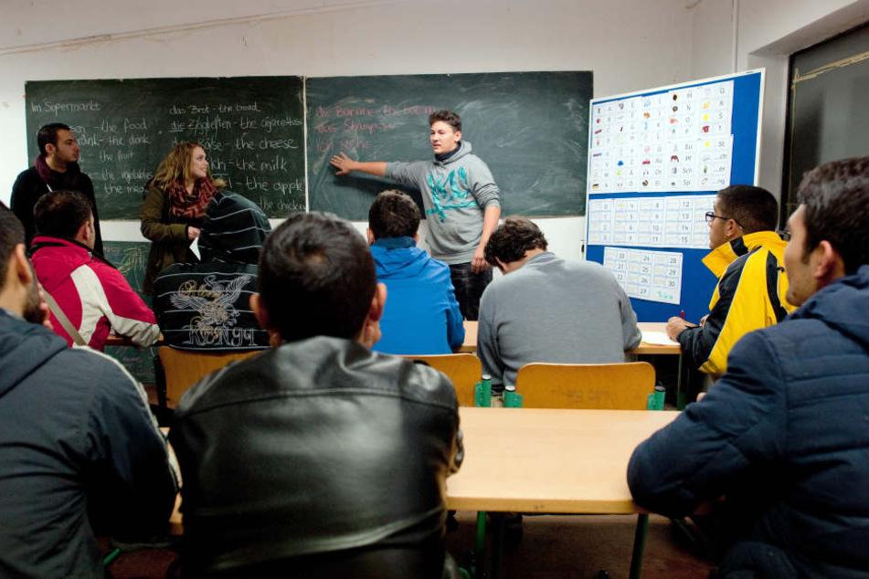 Der Syrer Shadi Tello (l. n. r.) und die Schüler Diana Sosin und Florian Wendland unterrichten in Eisenhüttenstadt Asylbewerber im Fach Deutsch.