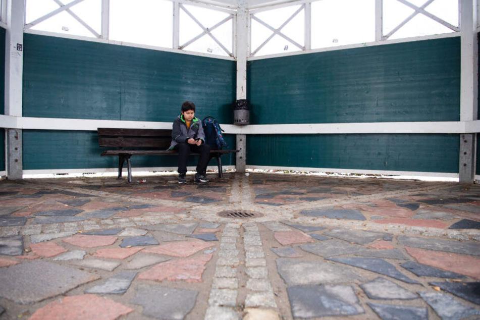 Marc wartet an einer Bushaltestelle auf sein Taxi.