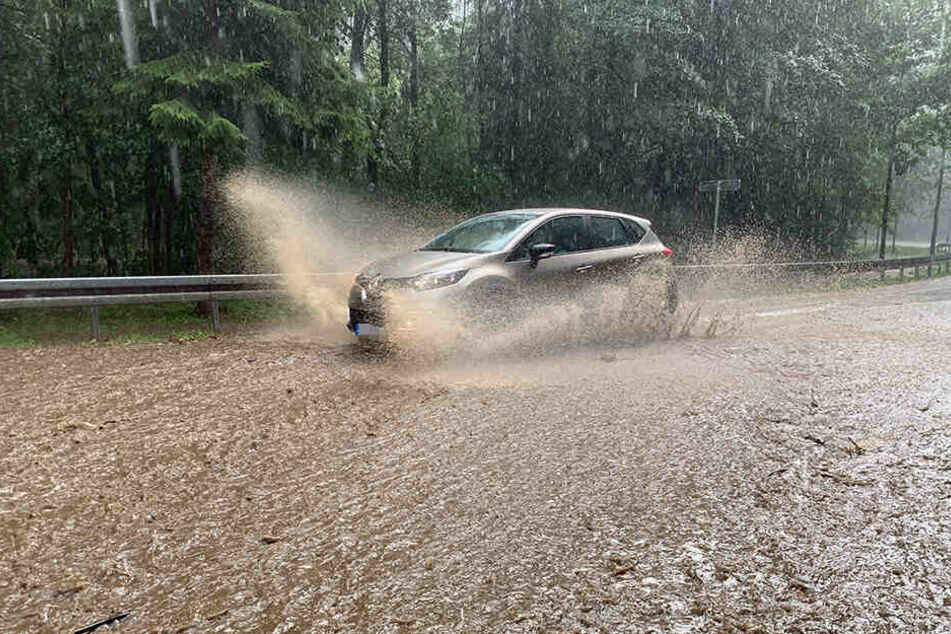 Ein Auto kämpft sich durch eine überflutete Straße.