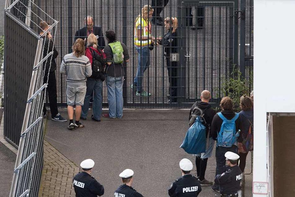 Aktivisten diskutieren mit Polizisten am Eingang zu einem Gate, an dem Flüchtlinge nach Afghanistan Kabul abgeschoben werden sollen.