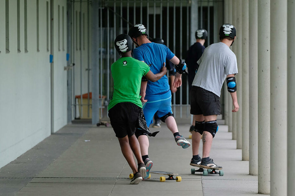 Ein Trainer der Gorilla Deutschland gGmbH (grünes Shirt) zeigt Häftlingen Übungen am Longboard. Die jungen Strafgefangenen hatten sich in einem Wettbewerb und den Freestyle-Workshop beworben und gewonnen.