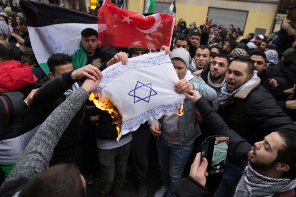 Teilnehmer einer Demonstration am 10.12.2017 verbrennen eine selbstgemalte Fahne mit einem Davidstern im Stadtteil Neukölln.