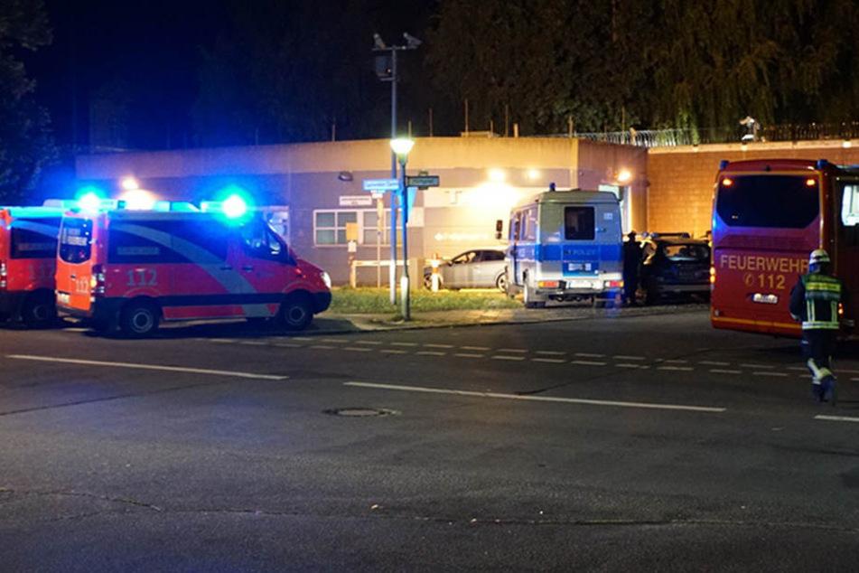 Mehrere Einsatzwagen der Feuerwehr und Polizei stehen vor dem Tor 1 der Justizvollzugsanstalt Plötzensee.