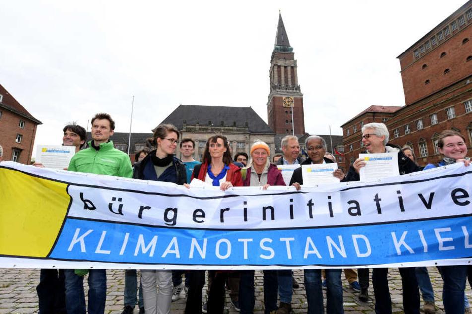 """Mitglieder der Bürgerinitiative """"Klimanotstand Kiel"""" stehen vor dem Rathaus. Die Bürgerinitiative stellte hier ihre Resolution mit Forderungen für die Landeshauptstadt Kiel zur Erklärung des Klimanotstands vor."""