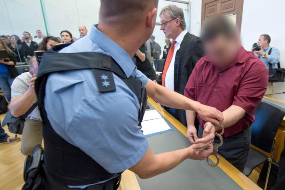 Der 42-jährige Angeklagte wird zur Anklagebank im Verhandlungssaal des Landgerichts in Gießen geführt.