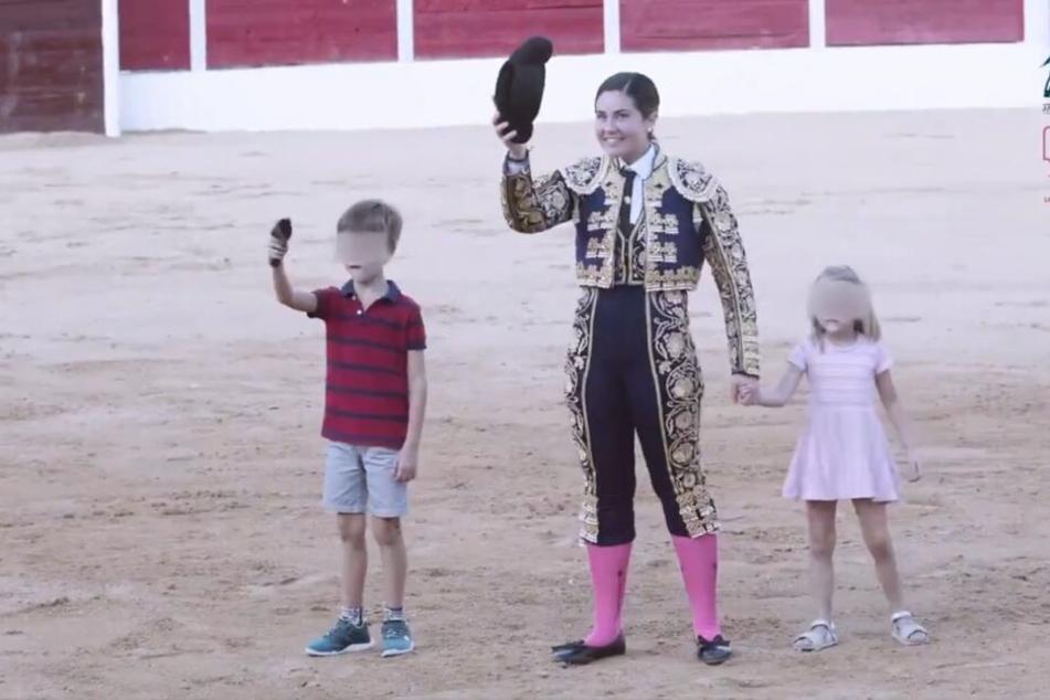 Stolz präsentiert sich eine Stierkämpferin dem Publikum. Ein Junge hält ein abgetrenntes Ohr in der Hand.