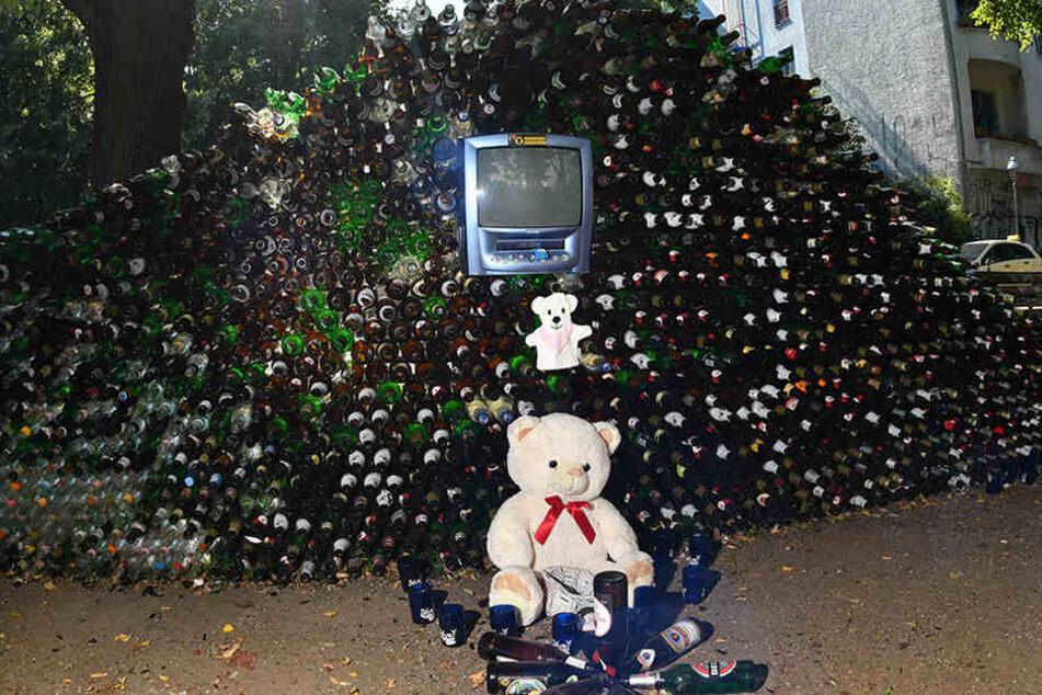Ein Teddy-Bär ziert die Front der Wand aus Glasflaschen.