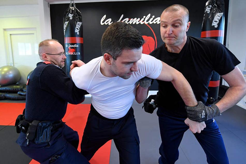 Bei einem Sicherheitstraining versuchen zwei Bahn-Mitarbeiter ihren Ausbilder Stefan Mederake (M.) zu überwältigen, der einen Randalierer spielt.
