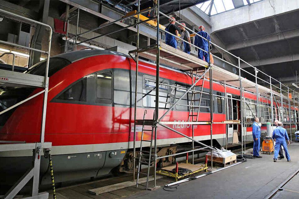 Mitarbeiter der Erzgebirgsbahn montieren Zusatzaggregate auf das Dach eines Triebwagens der Baureihe 642.