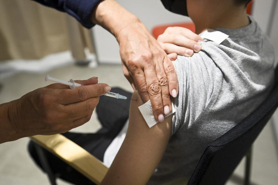 Ein zwölfjähriger Junge erhält eine Dosis des Corona-Impstoffs von Biontech/Pfizer.