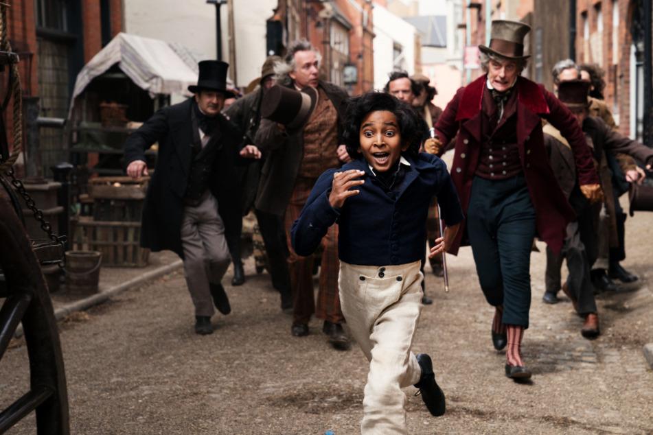 Auf der Flucht: David Copperfield (vorne; Jairaj Varsani) flieht gemeinsam mit Mr. Micawber (vorne-rechts; Peter Capaldi) vor den vielen Schuldeneintreibern.