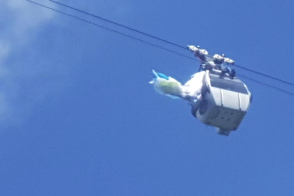 Dramatische Szenen: Gleitschirmflieger bleibt in Seilen von Gondel hängen