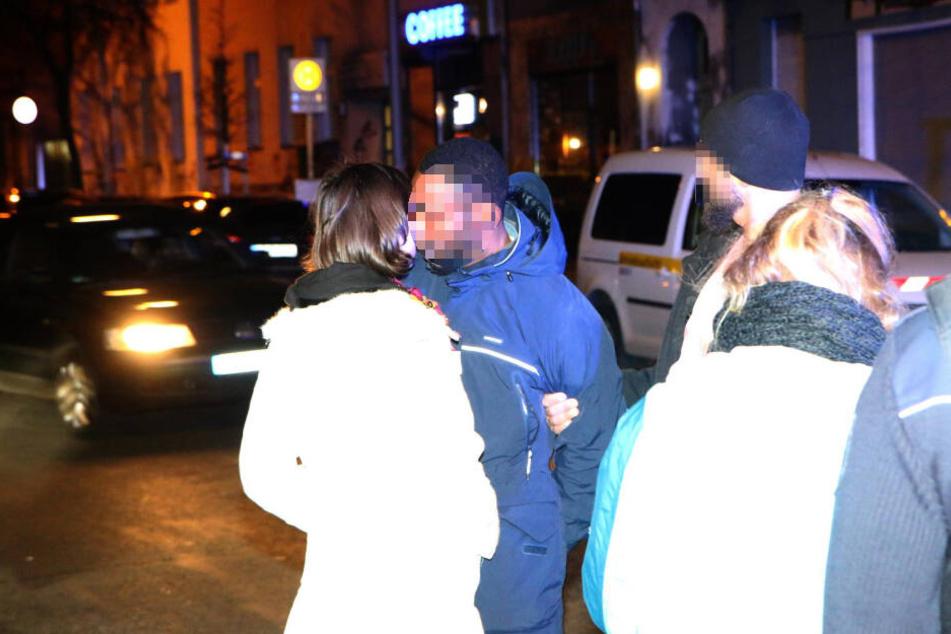 Mit Handschellen auf dem Rücken gibt der Mann seiner Begleiterin einen Kuss auf die Wange.