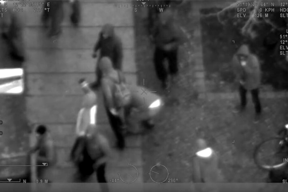 Die Aufnahme stammt aus einem Polizeihubschrauber und zeigt Randalierer, die einen Fußweg aufbrechen, um an Steine heranzukommen.