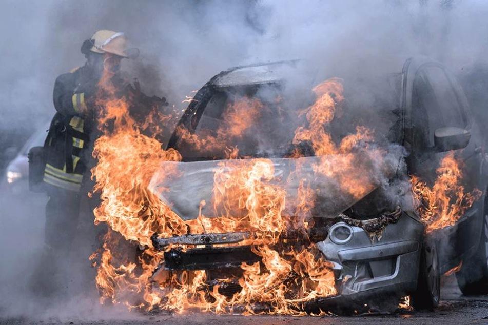 Ein Feuerwehrmann löscht ein brennendes Auto (Symbolbild).
