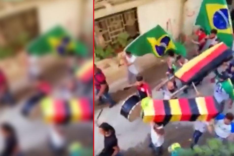 Brasilianische Fußball-Fans tragen deutsche Särge durch die Straßen.