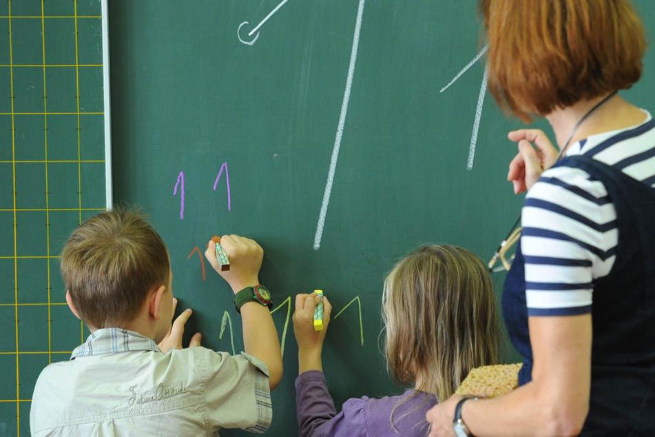 """Unter Anleitung der Klassenlehrerin schreiben zwei Grundschüler die Zahl """"Eins"""" an die Tafel."""