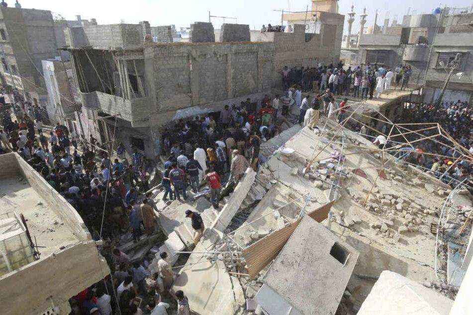 Menschen stehen an einem eingestürzten Gebäude, an der Einsturzstelle arbeiten Rettungshelfer.