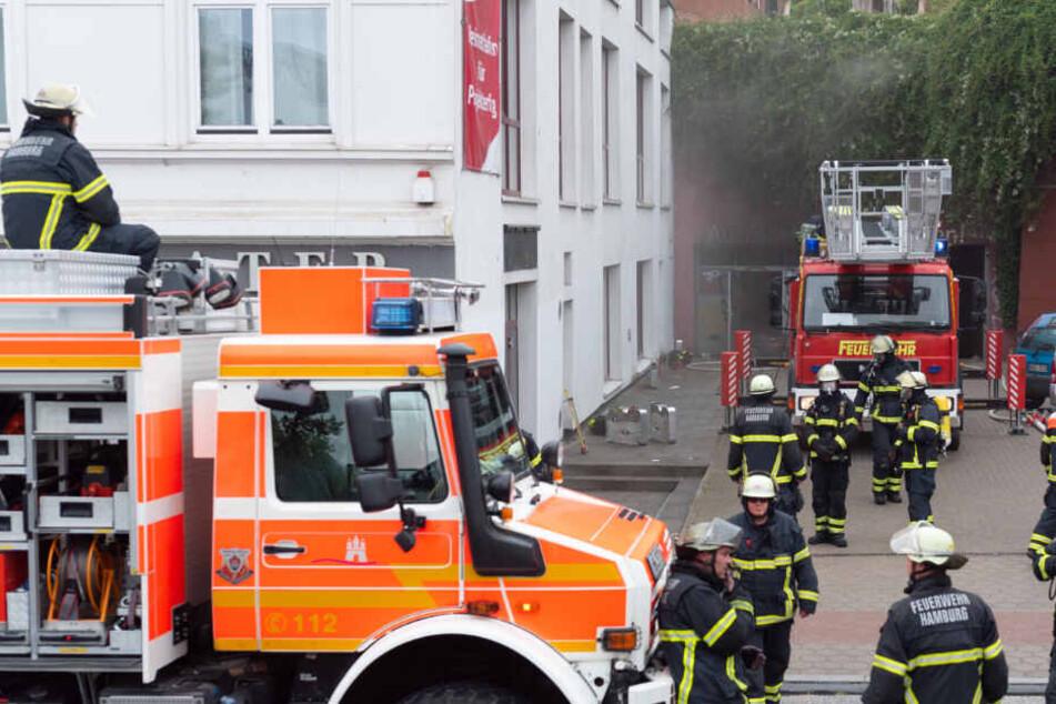 Der Qualm quoll aus der Tiefgarage, zahlreiche Feuerwehrmänner warten auf ihren Einsatz.