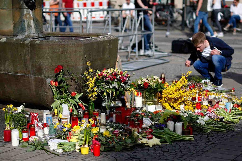 Ein Mann legt am Tatort in Münster Blumen ab.