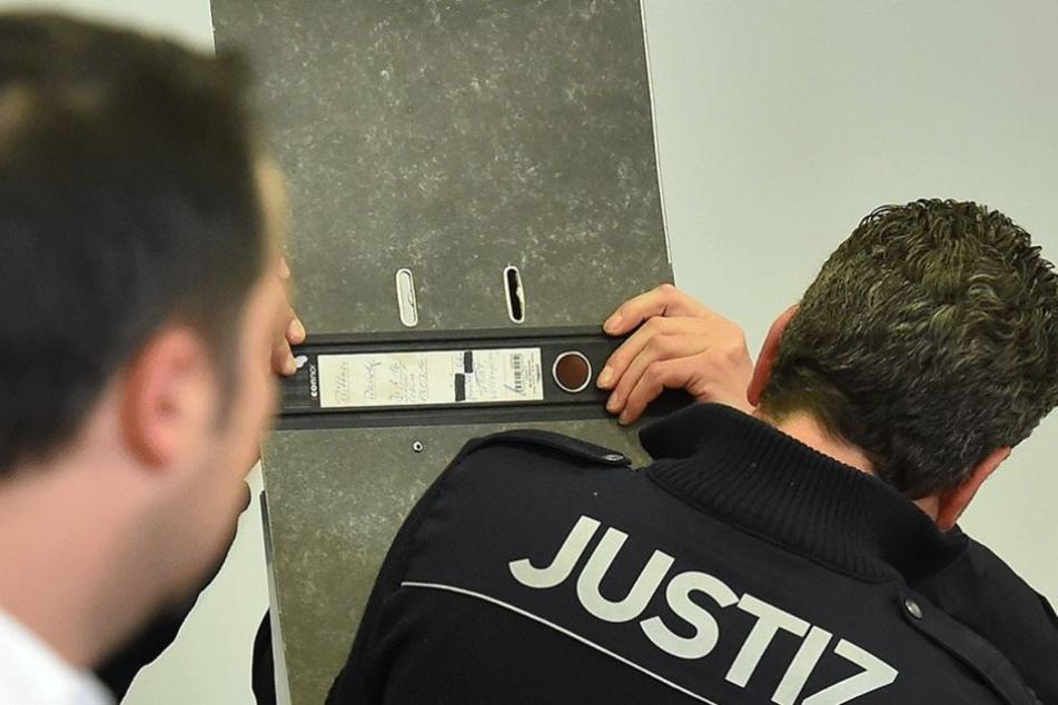 Der NPD-Politiker und Angeklagte Mail Schneider versteckt sein Gesicht hinter einem Aktenordner.