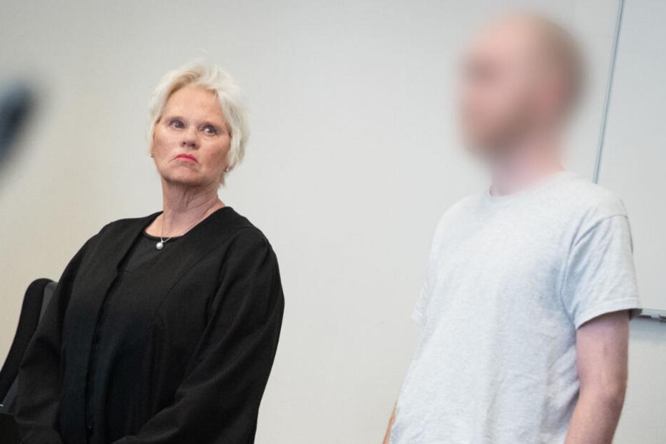 Der Angeklagte steht zu Beginn eines Prozesstages neben seiner Anwältin Anenette Voges im Gerichssaal des Strafjustizgebäudes.