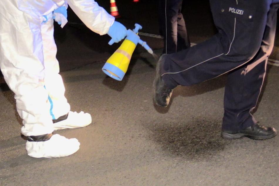 Ein Feuerwehrmann desinfiziert die Schuhe eines Polizisten.