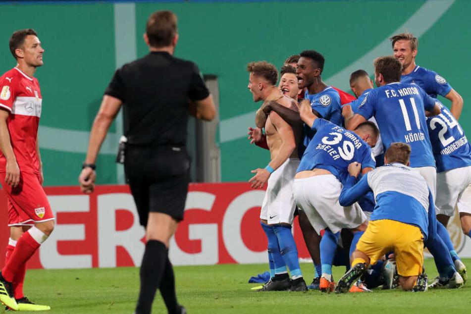 Die Rostocker feiern den Torschützen zum 2:0 Mirnes Pepic (nackter Oberkörper), rechts der Stuttgarter Christian Gentner. Der Drittligist besiegt den Erstligisten aus Stuttgart mit 2:0 (1:0).
