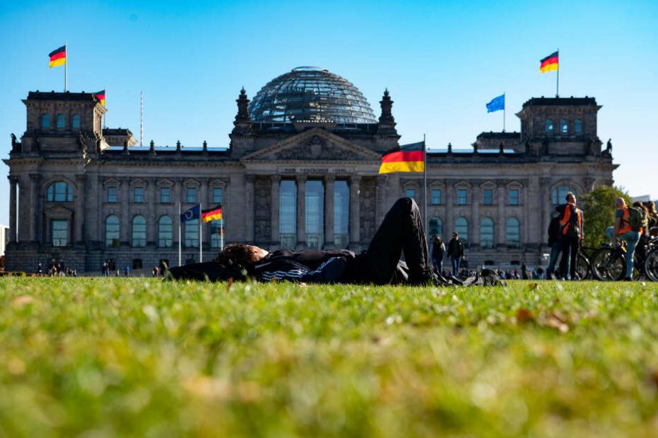 Eine Frau sonnt sich auf der Wiese vor dem Reichstag.