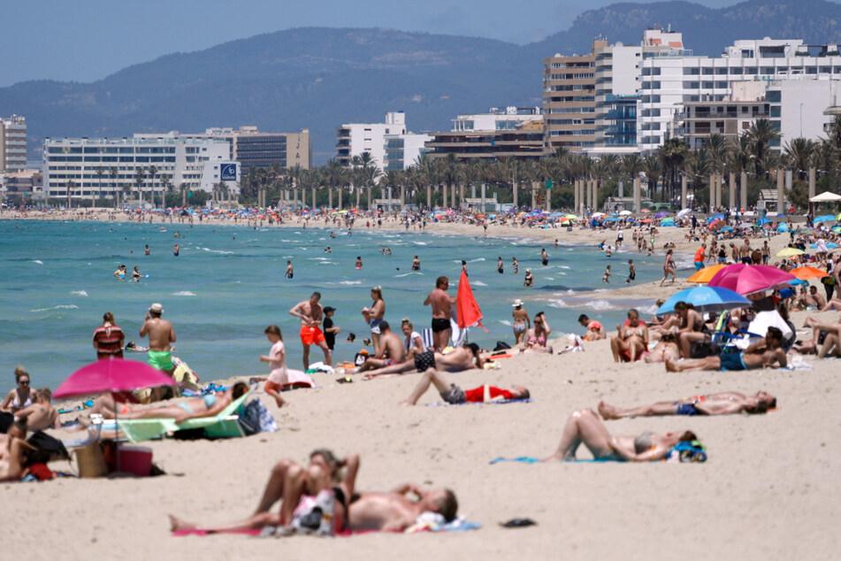 Spanien, Mallorca: Menschen sonnen sich am Strand von Arenal.