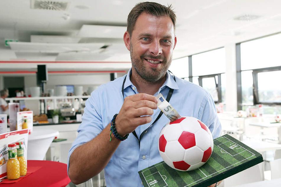 Symbolisch gleich mal fünf Euro rein! Matthias Krauß mit einem der FSV-Phrasen-Bälle.