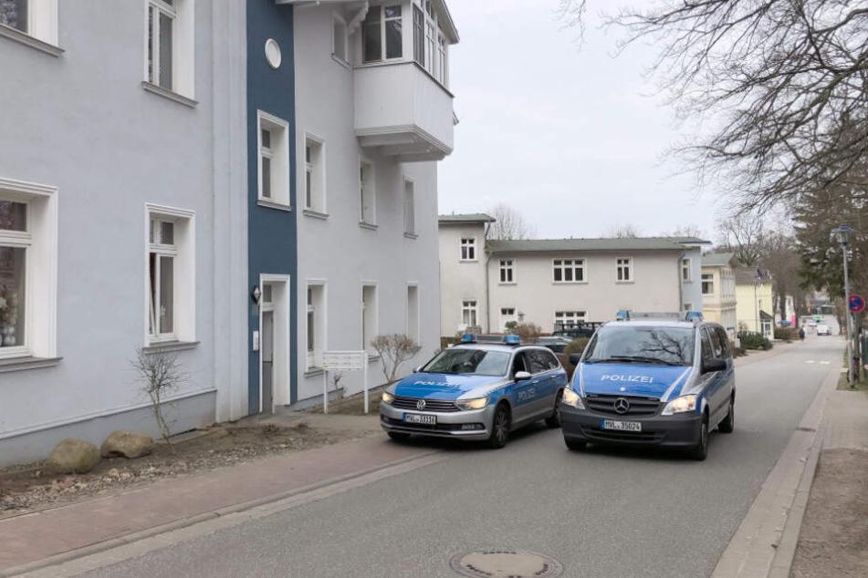 Einsatzfahrzeuge der Polizei stehen vor einem Wohnhaus, in dem eine junge Frau tot aufgefunden wurde.
