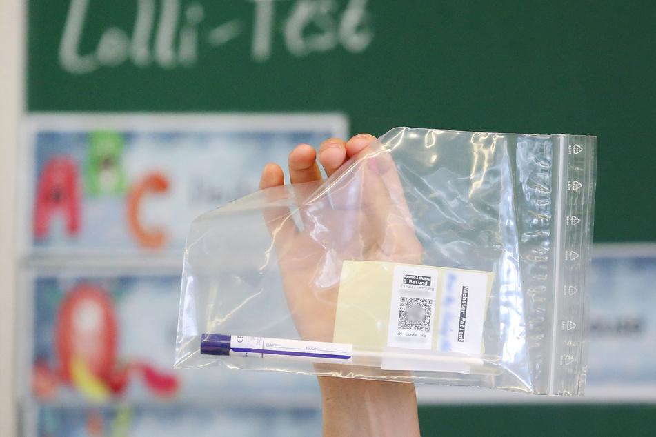 Einfach erklärt und schnell durchgeführt: Eine Lehrerin zeigt ihren Schülern den Lolli-Test.